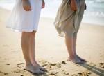 Two Women Standing Side by Side on Beach