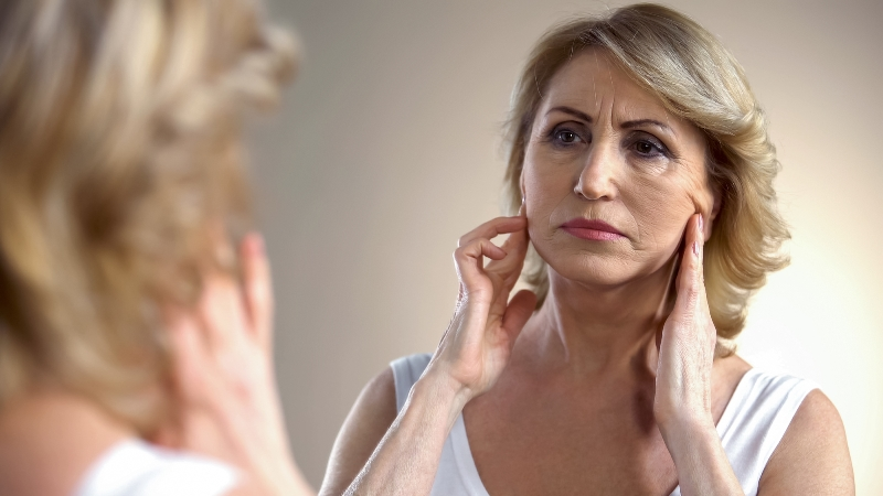 aging woman examining her face in the mirror